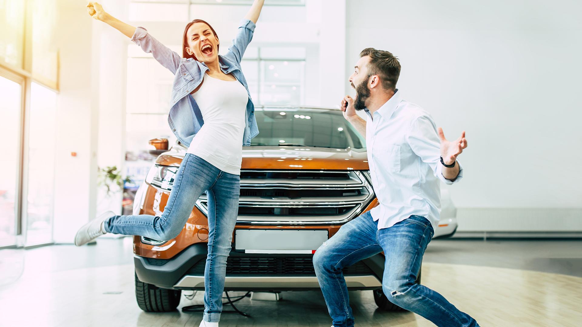 glückliches Pärchen beim Autokauf